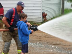 Firefighter Bellerose & student spraying water